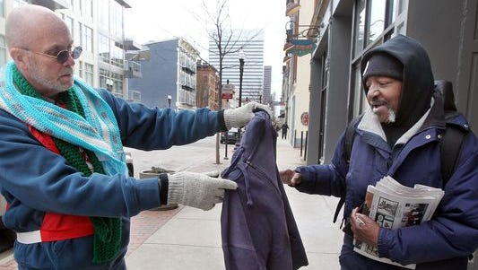 Larry Harvey, manager of emergency services for the Salvation Army, gives a sweatshirt to Lee McCoy in Over-the-Rhine in January.