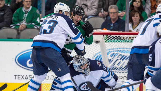 Winnipeg Jets goalie Ondrej Pavelec (31) makes a save as defenseman Ben Chiarot (63) checks Dallas Stars center Cody Eakin (20) during the third period at the American Airlines Center.