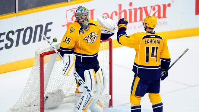 Nashville Predators goalie Pekka Rinne (35) celebrates with defenseman Mattias Ekholm (14) after a win against the Winnipeg Jets at Bridgestone Arena.