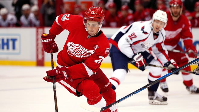 Dylan Larkin of the Red Wings controls the puck in front of Evgeny Kuznetsov of the Capitals during the third period at Joe Louis Arena on Feb. 18, 2017 in Detroit.
