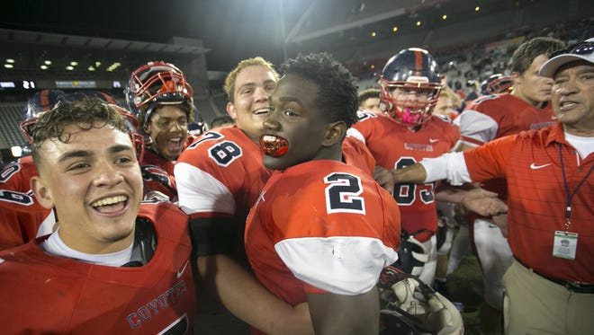 Centennial running back Alex Escobar (5), offensive lineman Daniel Thomas (78) and running back Zidane Thomas (2) celebrate after their 42-21 win over Notre Dame Prep during the 5A high school football state championship game at Arizona Stadium in Tucson on Saturday, December 2, 2017.