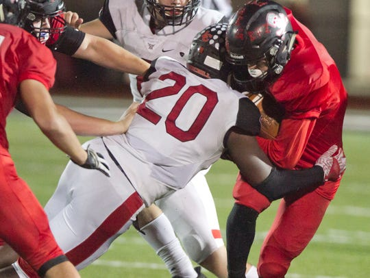 Livonia Churchill's Michael Parrish tackles Pinckney's Nick Cain, who had two touchdown catches.