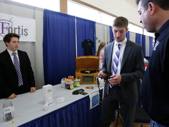 Co-owner Isaac Frieders, right, shows a patron making