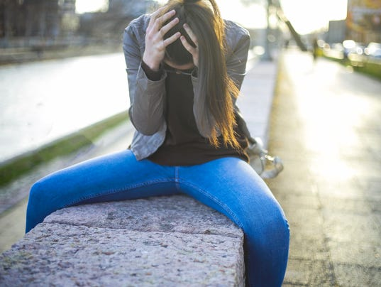 Young woman with headache - sitting outdoor holding head