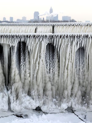 Ice from Lake Erie forms on a pedestrian walkway as the city of Cleveland is seen in the background, Thursday, Jan. 8, 2015, in Cleveland. Dangerously cold air has sent temperatures plummeting into the single digits around the U.S., with wind chills driving them even lower. (AP Photo/Tony Dejak)