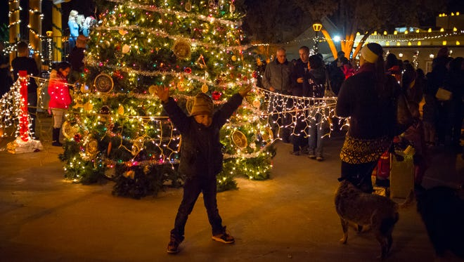 10-year-old Zeriyah Montoya poses in front of the Mesilla Plaza Christmas Tree during the tree lighting ceremony on Friday.
