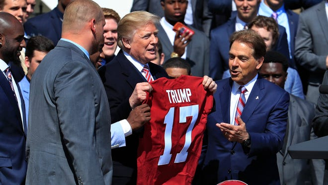 President Donald Trump holds up a team jersey presented to him by the 2017 NCAA football national champions, the Alabama Crimson Tide, during a ceremony honoring the champions on the White House's South Lawn, in Washington, Tuesday, April 10, 2018. On the right is head coach Nick Saban. (AP Photo/Manuel Balce Ceneta)