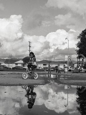 Girl in her bike playing in Closter Park in East Salinas with dramatic skies in the backround.