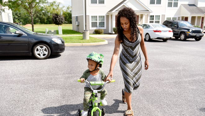 Kenyetta Redman helps her 3-year-old son ride a bike outside their Dover Township home on Friday, Aug. 25, 2017. In October 2013, Redman was five months pregnant when Jordan Breeland, her boyfriend and the father of her child, was shot and killed in York.