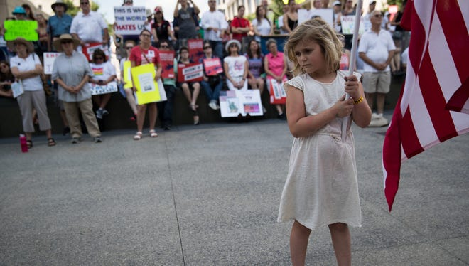 Josephine Shaver, 8, of Indianapolis, holds a U.S. flag as she attends an immigration protest at the Indiana Statehouse organized by the ACLU, Indianapolis, Saturday, June 30, 2018.