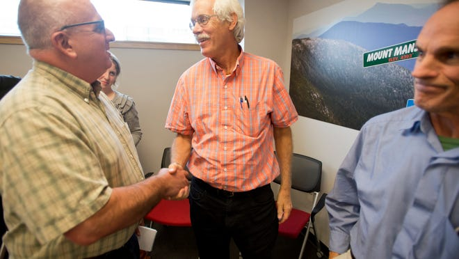 Veteran Burlington Free Press reporter Sam Hemingway is congratulated Tuesday by colleagues Dan D'Ambrosio, left, and Tim Johnson, right, after announcing his retirement.