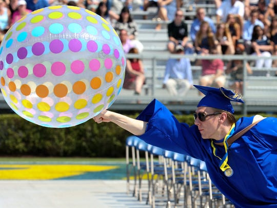 Dylan Miller of Wilmington does his part to keep a beach ball in play as the University of Delaware confers degrees on about 5800 students during commencement at Delaware Stadium Saturday.