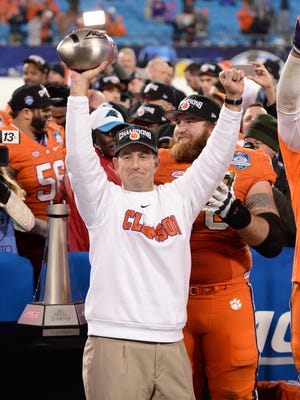 Clemson head coach Dabo Swinney holds the ACC Championship trophy after the Tigers 45-37 win over North Carolina in the ACC Championship at Bank of America Stadium in Charlotte Friday, Dec. 4, 2015.