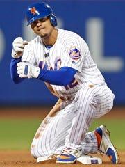 New York Mets' Juan Lagares gestures toward the dugout
