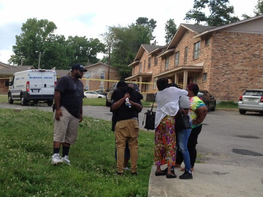 People embrace near the spot where 27-year-old Dominique White was fatally shot. The mourners included Katie White (in dress), grandmother of the victim.