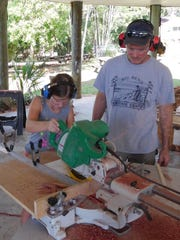 Eleven-year-old Dorothy Palmer uses the miter saw with supervision from Ken Horne.