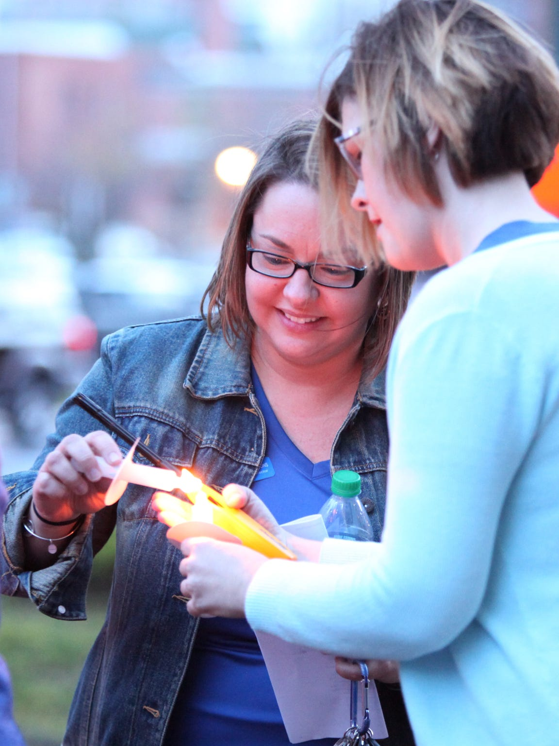 Valley Children's Advocacy Executive Director Rebecca Simmons lights candles with other staff members during a vigil for child abuse victims at the Augusta County Courthouse in Staunton.