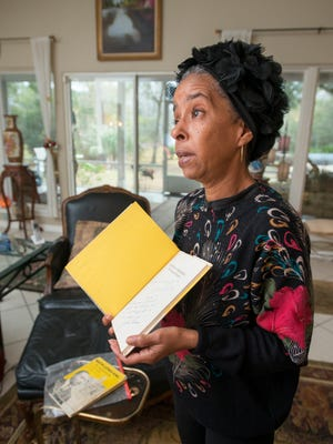 Jawana Jackson shows a book that was inscribed to her by Dr. Martin Luther King Jr. and Jackie Robinson during an interview at her home in Milton on Thursday, Jan. 11, 2018.