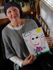 """Breast cancer survivor Fronda Alley shows off the album cover art that accompanies her song """"I've Got No Hair."""" Her 8-year-old son drew it."""