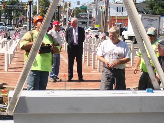Freehold, NJ - Jim Donechie, Jr. and Freehold mayor Nolan Higgins watch as workers install the Freehold WWII Honor Roll Memorial Monument in downtown Freehold, at the intersection of Route 79 and Route 537.
