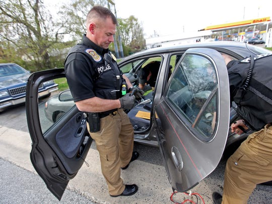 Lt. Jim Unger, commander of the New Castle County Police Department's Mobile Enforcement Team, search a vehicle pulled over on a traffic violation and suspicion of drugs along Halcyon Drive off Route 9 in New Castle.