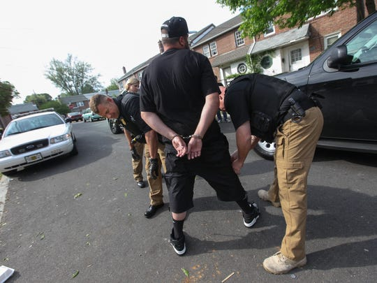 Officers with the New Castle County Police Department's  Mobile Enforcement Team search a suspected drug dealer.