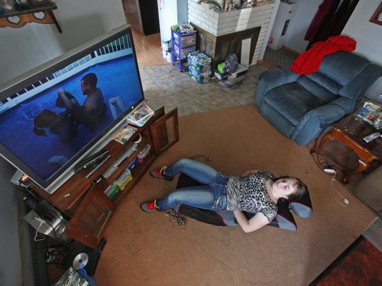 Danielle Eby watches old home videos of her parents playing in the pool with her as an infant.