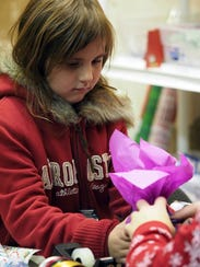 Isabella Liviskie puts the finishing touches on a gift