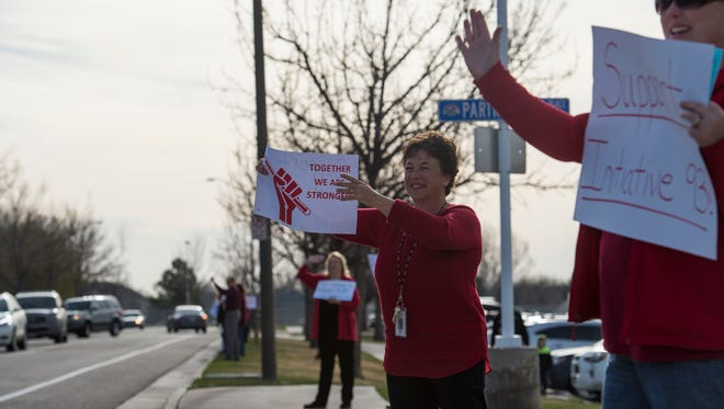 """Second grade teacher Janet Hanlon and kindergarten assistant Sara Hart wave to passing traffic while holding signs with other employees of the school during a """"walk-in"""" on Monday morning, April 16, 2018, outside of Traut Core Elementary School in Fort Collins, Colo. Some PSD teachers are planning to head to Denver April 27 to continue advocating for more education funding."""