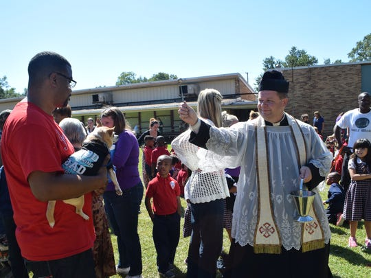 Kenneth Coleman (left), holds Chico, the family pet, as the Rev. Chad Partain (right) of St. Frances Cabrini Church in Alexandria blesses the Chihuahua. Students and parents at St. Frances Cabrini School brought their pets to be blessed Friday on the school grounds. Coleman's son Kenterrus Coleman is a student at the school.
