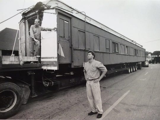 Rob Carr, left, and Scott Jubeck, assistant manager, help direct the parking of the train coach that was delivered by Carr to Clara's in downtown Lansing, June 15, 1994.