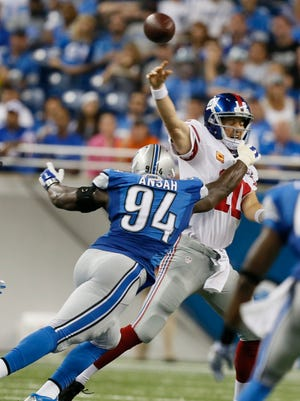Giants quarterback Eli Manning completes a pass as he is hit by Lions defensive end Ziggy Ansah in the second quarter at Ford Field on Monday, Sept. 8, 2014.