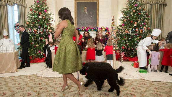 First lady Michelle Obama walks with dogs Bo (back)