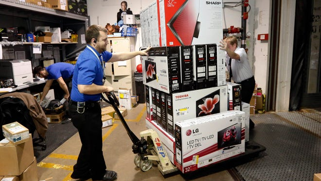 Chris Busch, left, unloads electronics from a truck Nov. 26 for Black Friday sales at a Best Buy store in Oklahoma City.