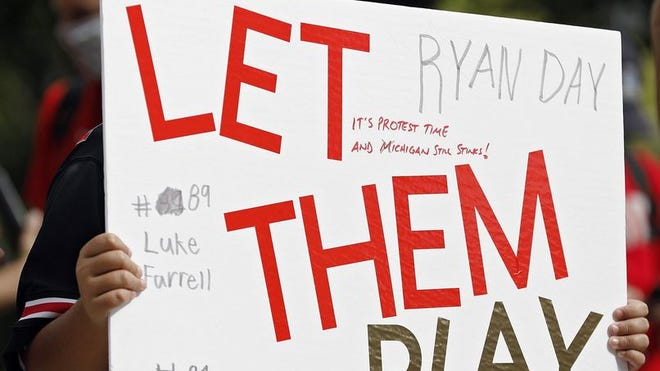 Graham Fleck, 11, of Grove City holds a sign during a rally organized by parents of Ohio State football players outside the rotunda of Ohio Stadium on Aug. 29.