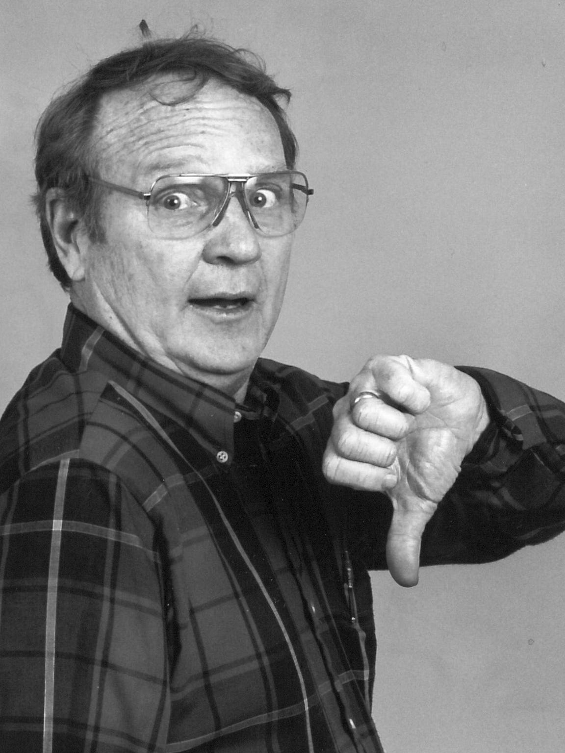 "Film critic Bob Lapham, his hair askew, practices his ""thumb's down"" pose."