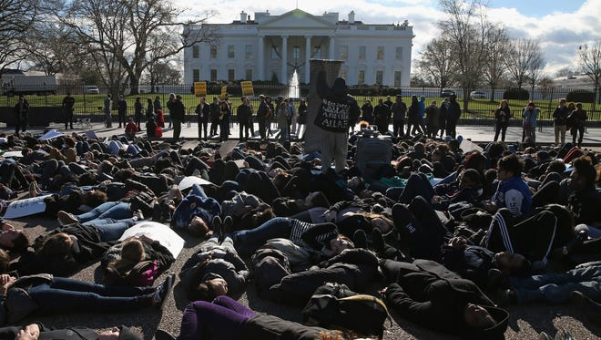 """Students from The School Without Walls in Washington, D.C., participate in a """"die in"""" during a protest in front of the White House, Dec. 17, 2014. The students were protesting recent grand jury decisions not to indict police officers in the killings of unarmed black men in Ferguson, Missouri and Staten Island, N.Y."""