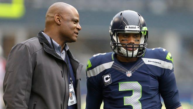 Seattle Seahawks quarterback Russell Wilson (3) talks with former Seahawks quarterback Warren Moon, left, who is currently a Seahawks broadcaster.