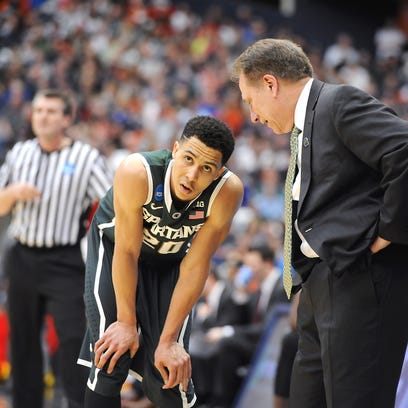 A hurting Travis Trice rests next to head coach Tom