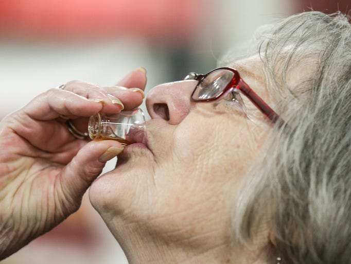 Linda Thomas tastes Montana Honey Moonshine from the