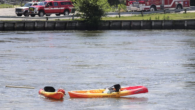 Two kayaks remain in the water at the Racine Street bridge near the Menasha dam after two kayakers became stranded, clinging to a cable, in the fast water near the dam on Friday, June 23, 2017 in Menasha.