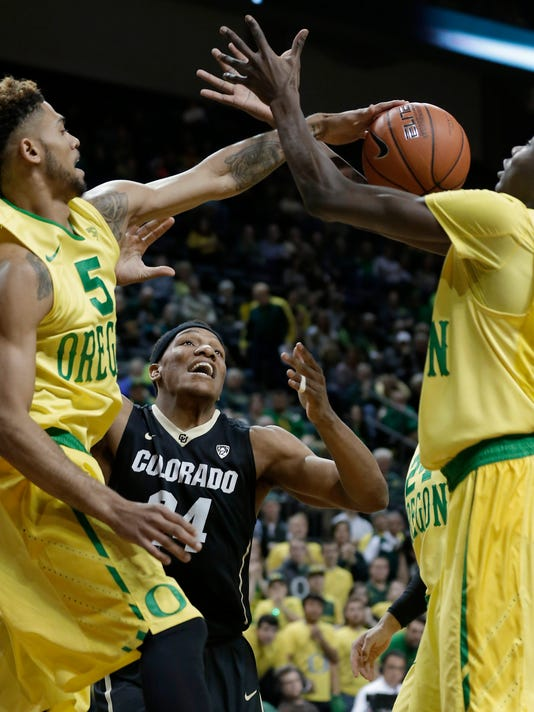 Oregon's Tyler Dorsey, left, pushes the rebound to Oregon's Chris Boucher, right, in front of Colorado's George King during the first half of an NCAA college basketball game Thursday, Feb. 4, 2016, in Eugene, Ore. (AP Photo/Ryan Kang)