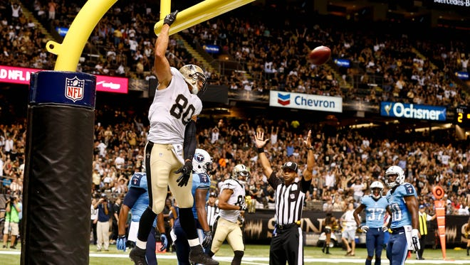 New Orleans Saints tight end Jimmy Graham (80) celebrates by dunking over the goalpost following a touchdown against the Tennessee Titans during second quarter of a preseason game at Mercedes-Benz Superdome.