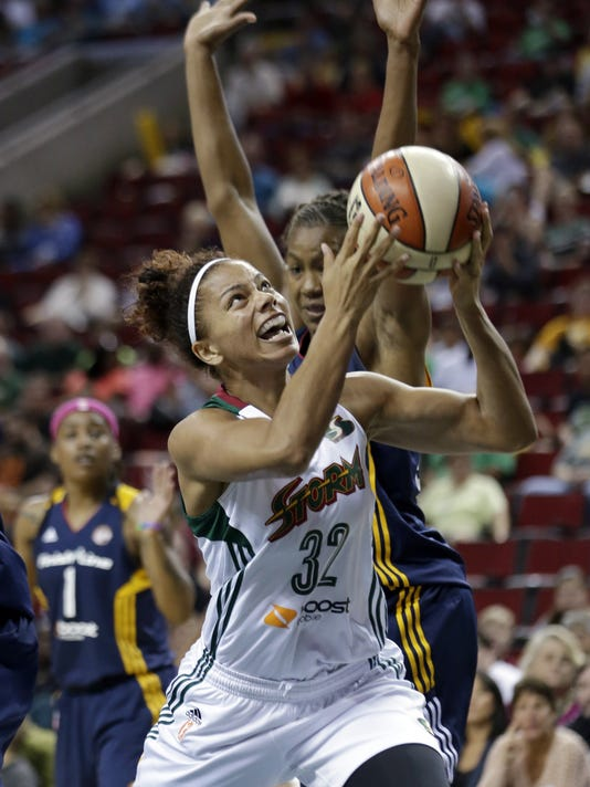 Seattle Storm's Alysha Clark (32) tries to drive past Indiana Fever's Tamika Catchings in the first half of a WNBA basketball game Thursday, July 31, 2014, in Seattle. (AP Photo/Elaine Thompson)