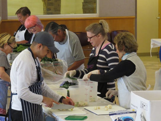 World Central Kitchen volunteers chop vegetables Monday in O'Brien Hall at San Buenaventura Mission in downtown Ventura.