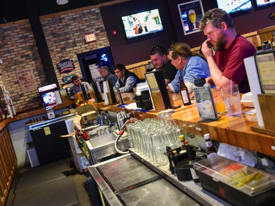 Customers relax at the bar and enjoy the games at Chicken Coop Sports Bar & Grill in Urbandale.