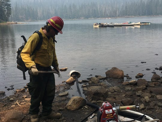Firefighters use water pumps to protect buildings at