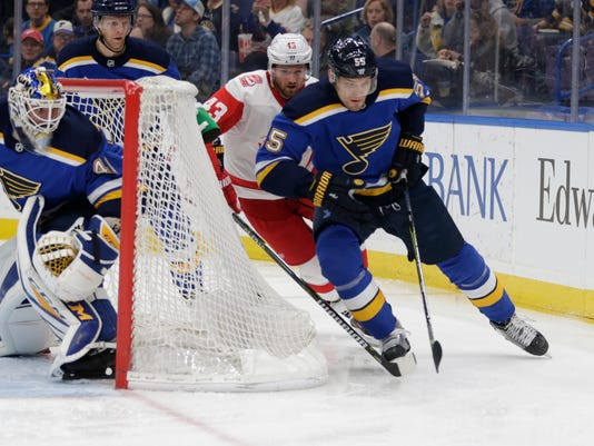St. Louis Blues' Colton Parayko (55) holds off Detroit Red Wings' Darren Helm (43) as they chase the puck behind the net as goaltender Carter Hutton (40) looks on in the first period of an NHL hockey game, Wednesday, Feb. 28, 2018 in St. Louis. (AP Photo/Tom Gannam)