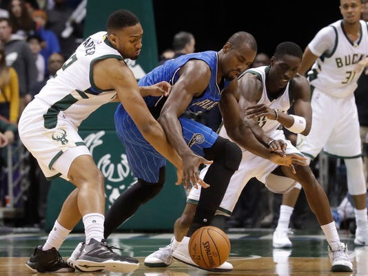 Milwaukee Bucks' Jabari Parker and Tony Snell battle for a loose ball with Orlando Magic's Serge Ibaka during the second half of an NBA basketball game Monday, Nov. 21, 2016, in Milwaukee. (AP Photo/Morry Gash)