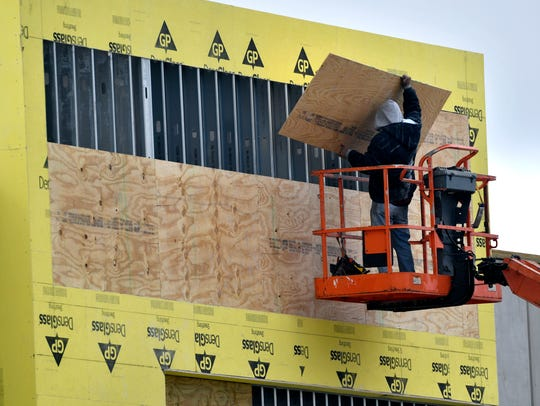 A worker places a plywood sheet on the facade of one of the stores under construction at the new Shops at Abilene Village shopping center in the 3500 block of South Clack Street.